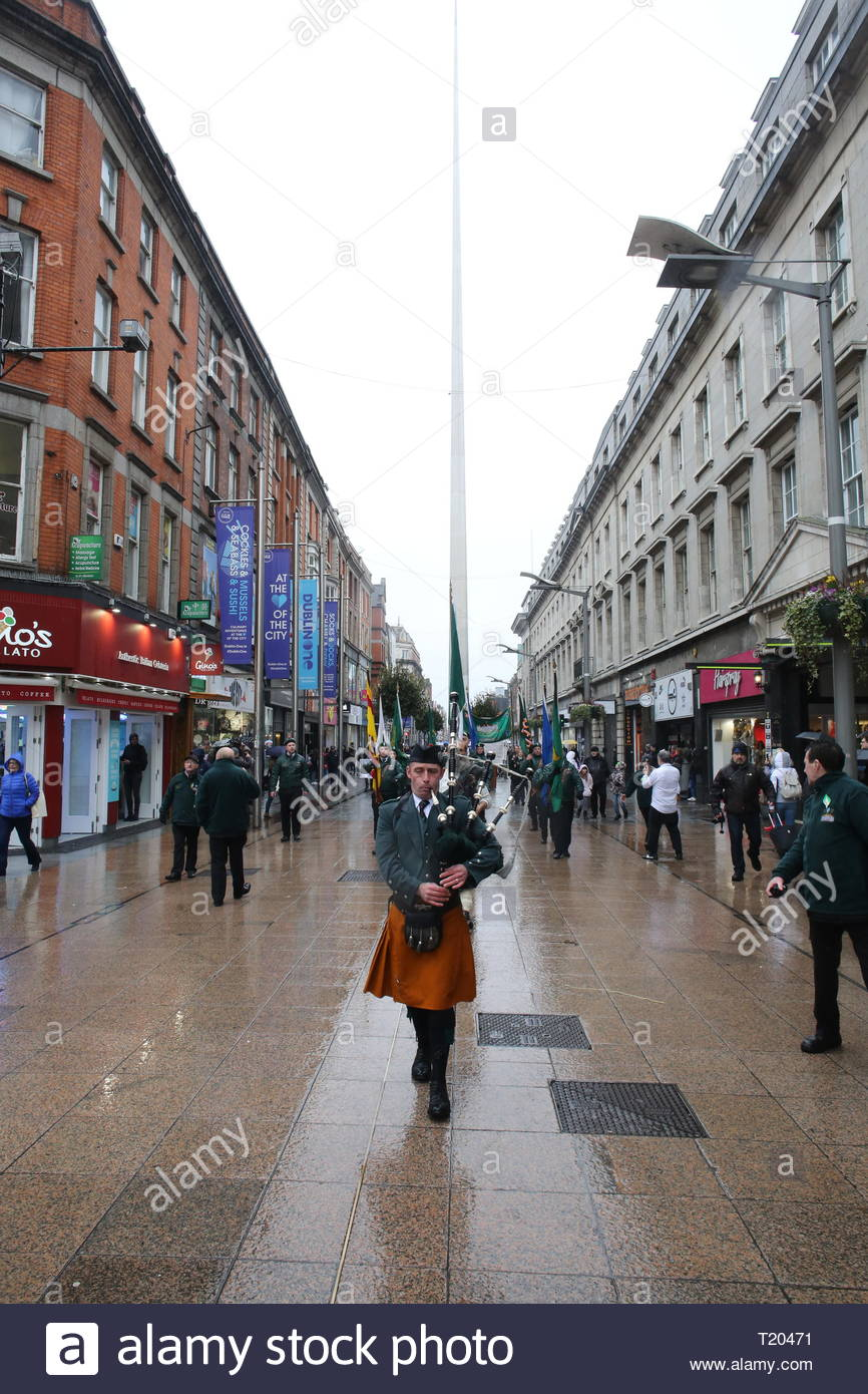 A lone piper leads a Republican march in honour of the 1916 Rising through the streets of Dublin at easter time. - Stock Image
