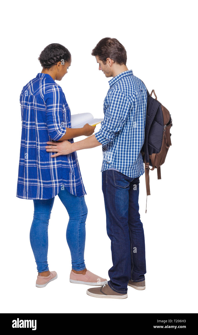 Back view of a multinational couple of students who are looking into a notebook. Rear view people collection. backside view of person. Isolated over w Stock Photo