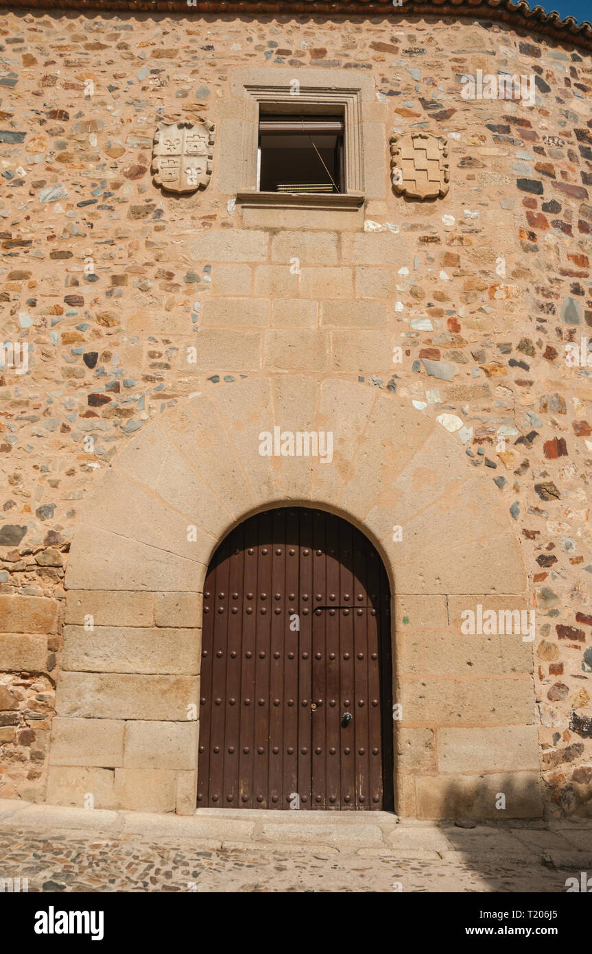 Wooden Door In Old Building Facade With Rounded Top Door Frame At Caceres.  A Charming Town With A Fully Preserved Old City Center In Spain.