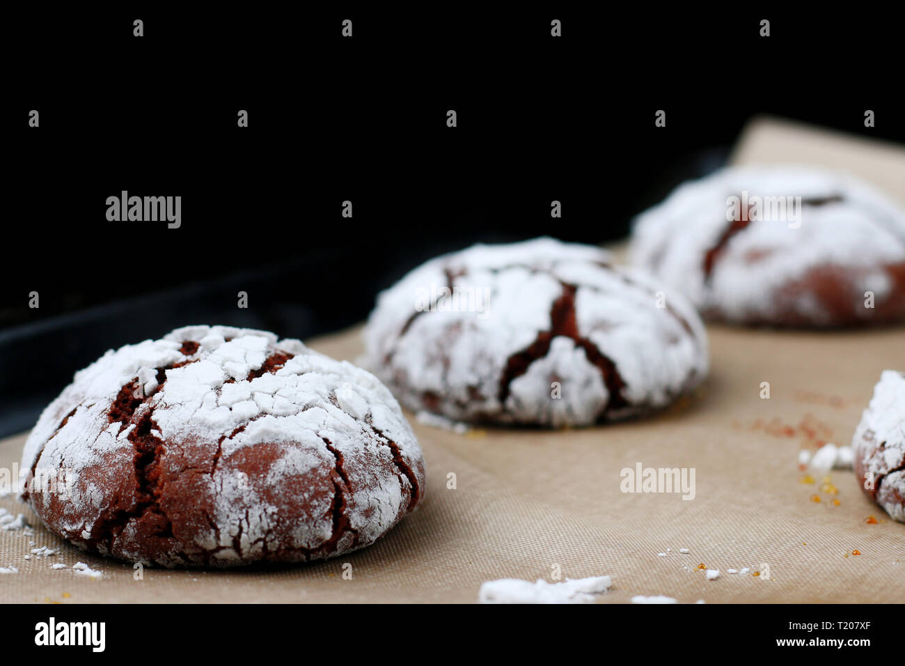 Chocolate cookies with cracks on baking paper and iolated on black. Cracked chocolate biscuits. Stock Photo