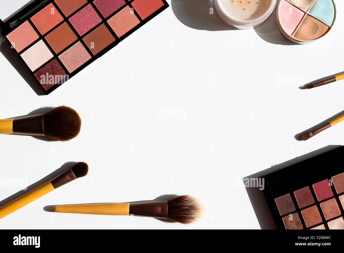Bright arrangement of make up cosmetics and accessories. Eyeshadow palettes, powder, concealer and natural brushes with bamboo wood handles. Copy spac Stock Photo
