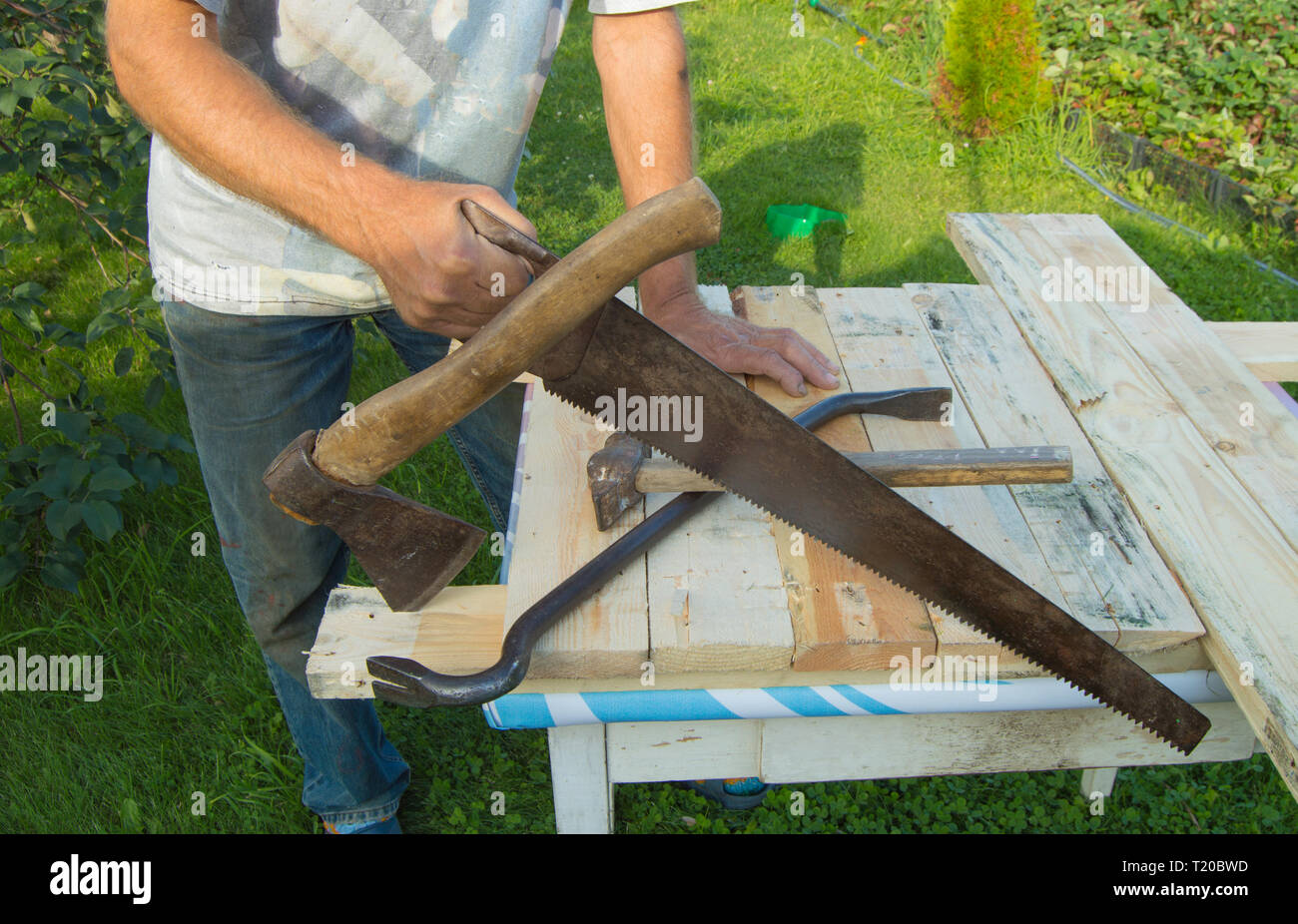 man uses a hacksaw, a hatchet, a claw hammer for construction work in your garden. - Stock Image