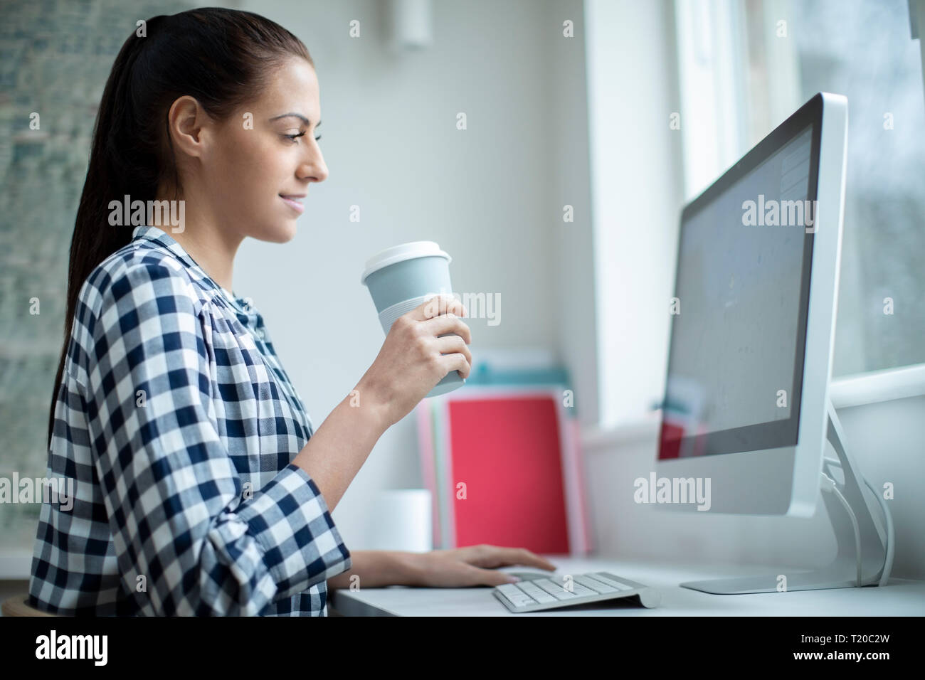 Woman Working At Computer Drinking From Reusable Takeaway Cup - Stock Image