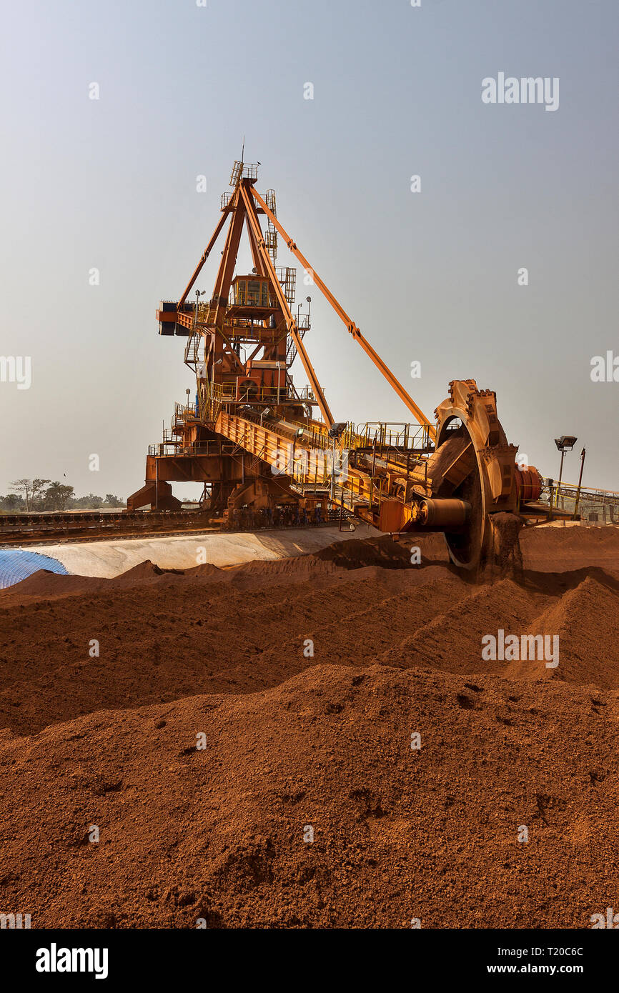 Port operations for managing and transporting iron ore.  Bucket  reclaimmer stacker using bucket wheel to move lump ore to conveyor before shipping. Stock Photo