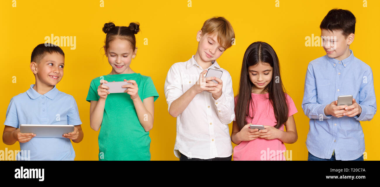 Gadget addiction. Children with modern gadgets standing over yellow background - Stock Image