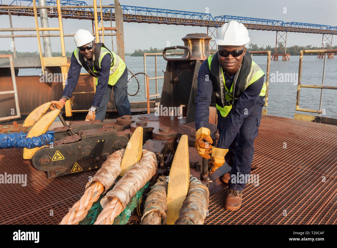Port operations for managing and transporting iron ore.  Dolphin jetty mooring facility with riggers using quick release rope hooks as ship sets sail - Stock Image