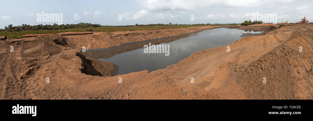 Port operations for managing and transporting iron ore. Future site extension with water area being reclaimed with sand from dredging sea channel Stock Photo
