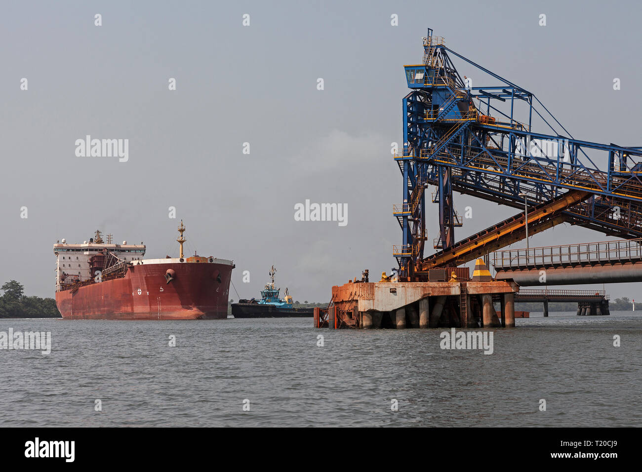 Port operations for managing and transporting iron ore.Tug manoeuvring and turning transhipment vessel before docking and loading up ore at jetty - Stock Image