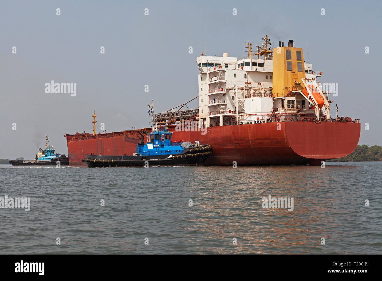Port operations for managing and transporting iron ore.Tugs manoeuvring and turning transhipment vessel before docking and loading up ore at jetty - Stock Image