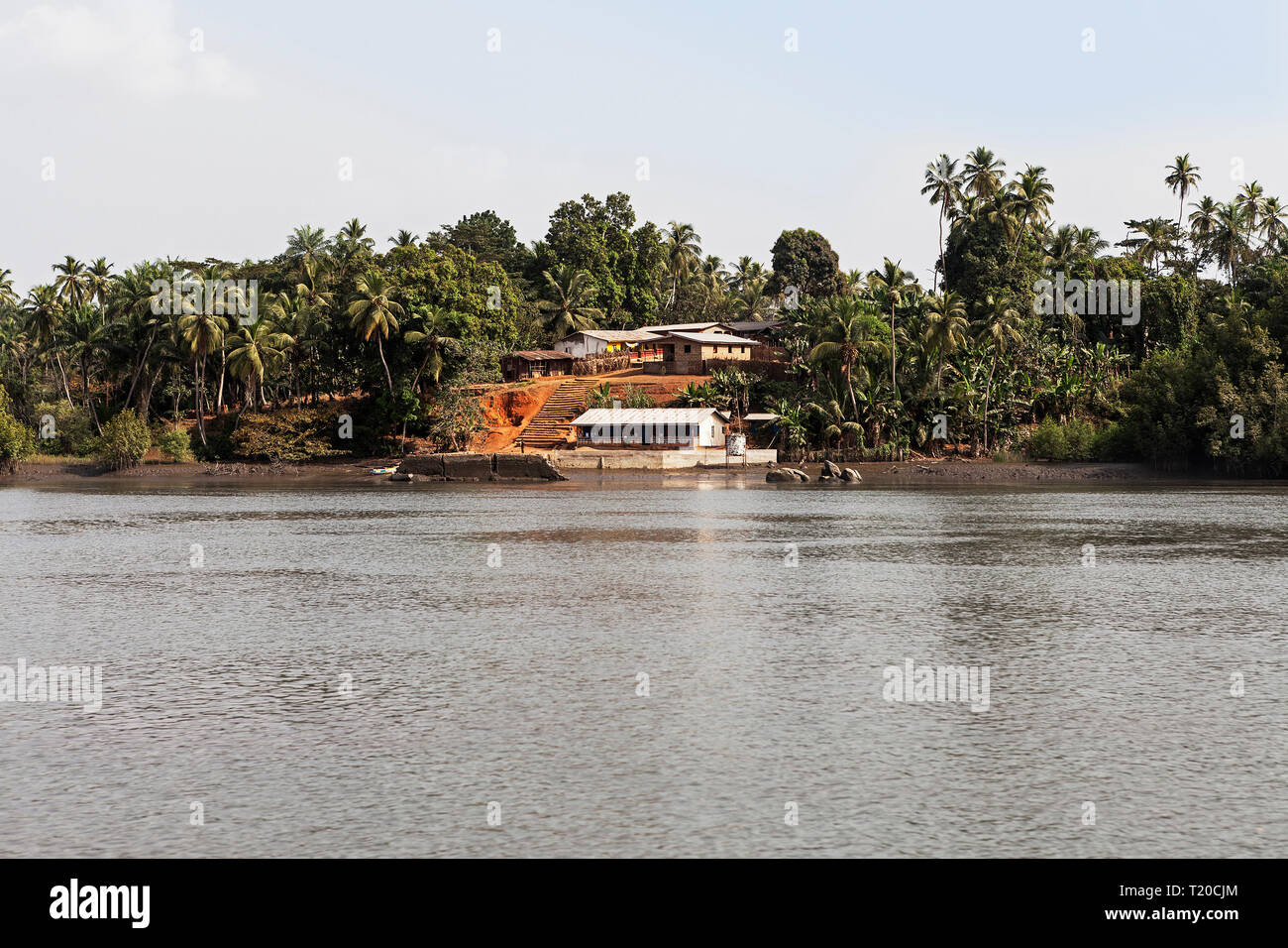 Lush tropical vegetation and African village up Port Loko Creek plus café restaurant at landing stage for small marine craft and boats, Sierra Leone Stock Photo