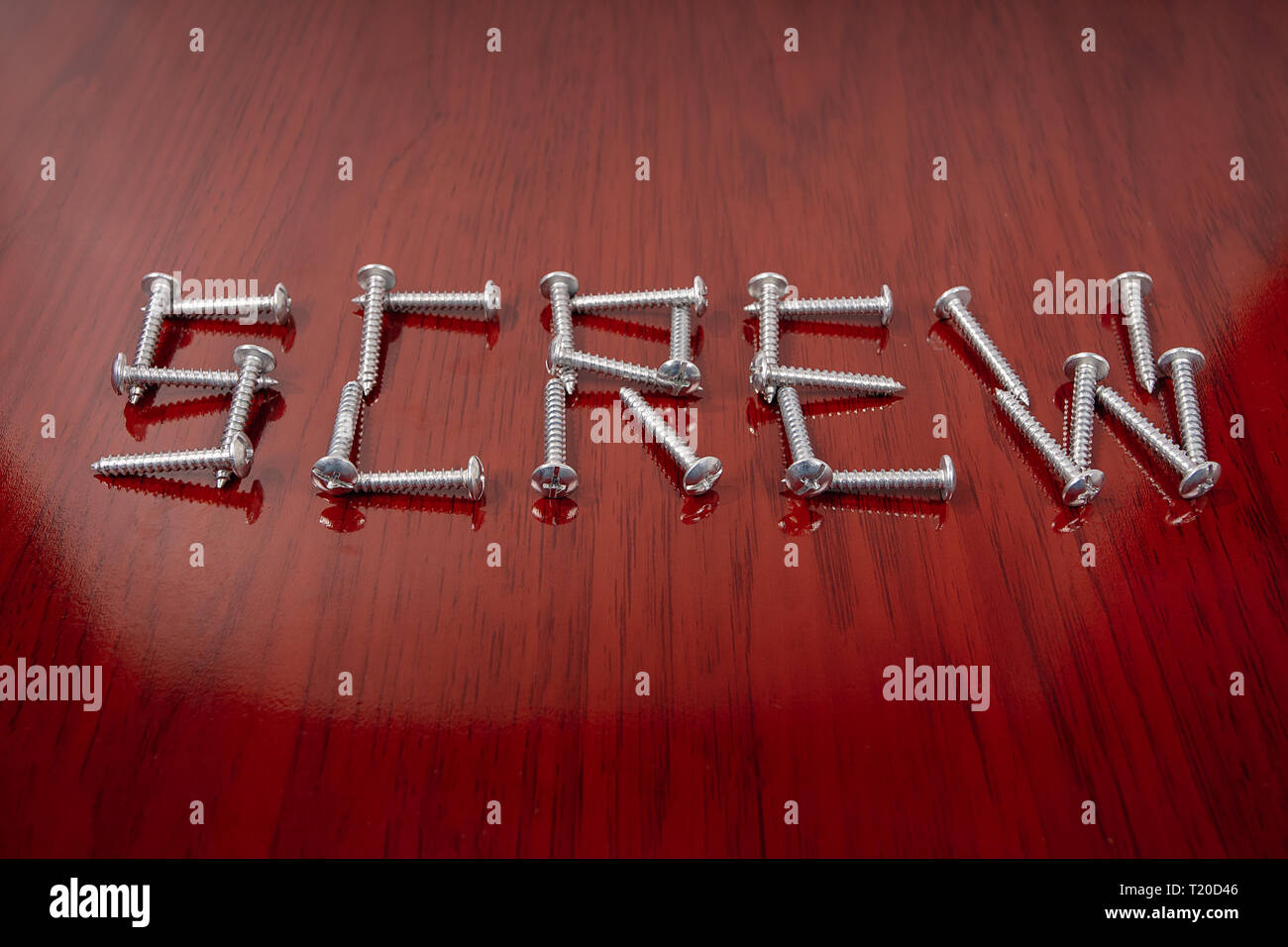 An organized group of screws forming the word screw - Stock Image