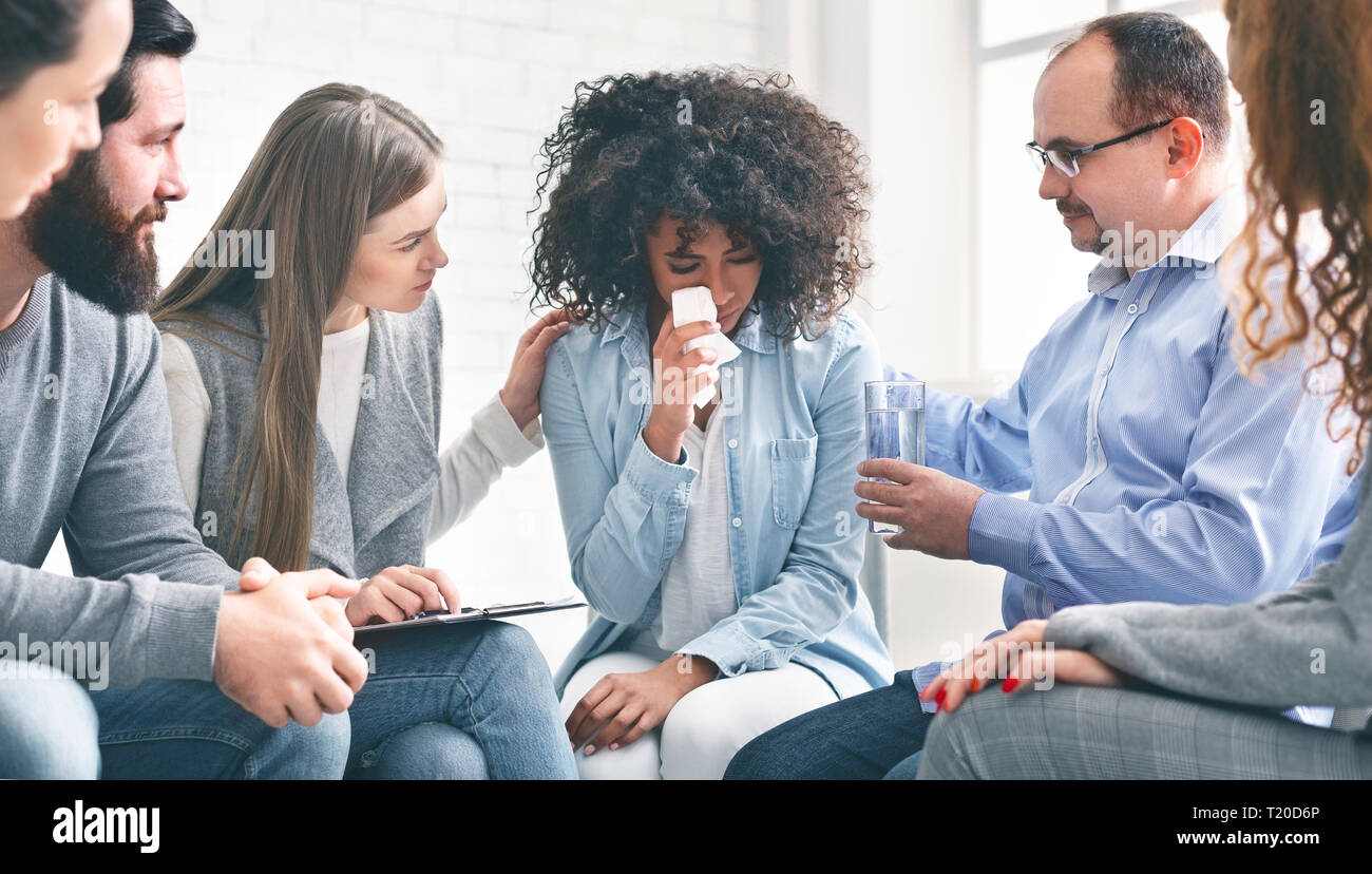 Young woman with emotional problems crying during psychotherapy Stock Photo