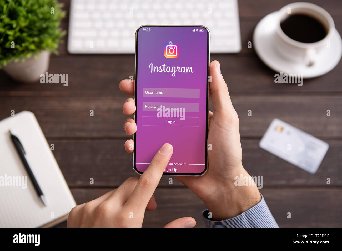 Man holding iPhone ack with Instagram application on screen. - Stock Image