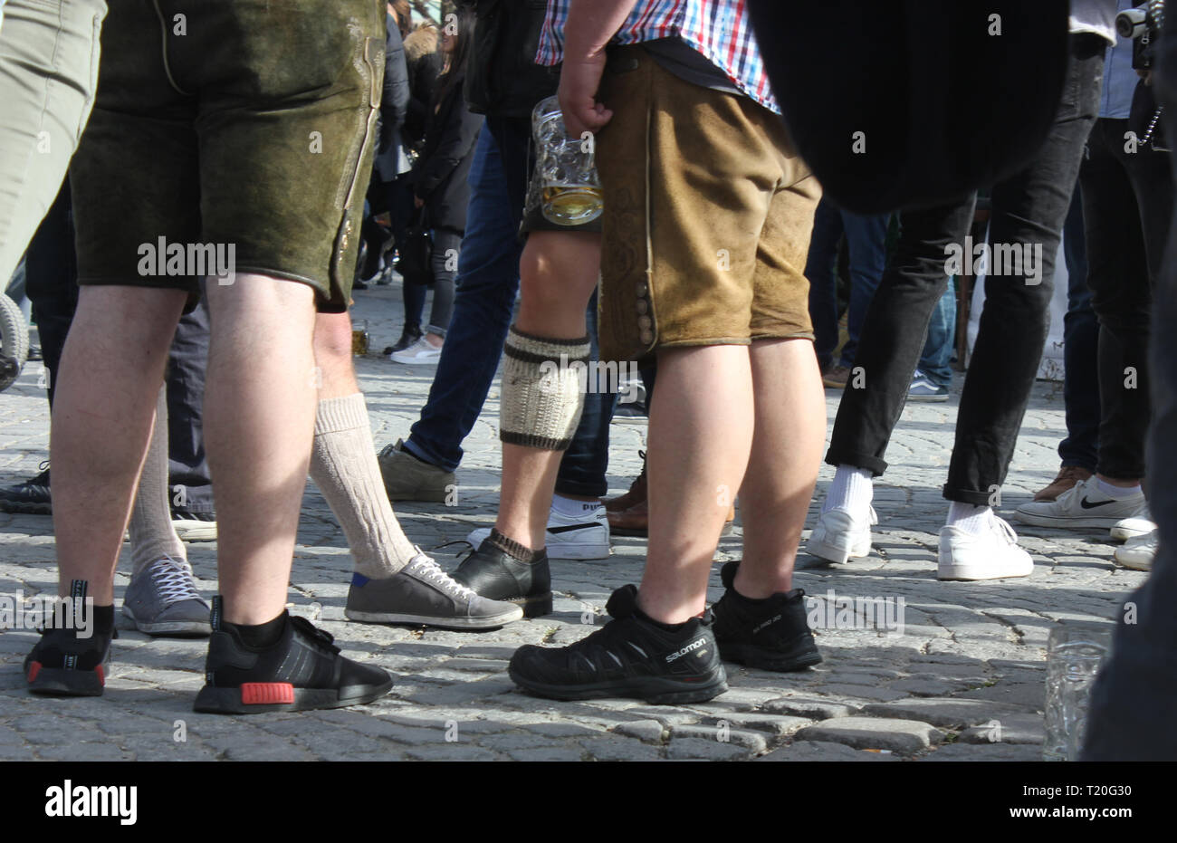 Boys dressed in bavarian Lederhosen. The bavarian fashion piece they mix up with casual sport shoes, one wears half stocking with Haferlschuh. - Stock Image