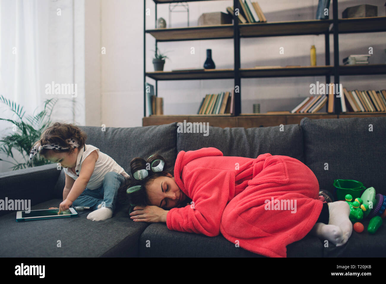 Young mother old is experiencing postnatal depression. Sad and tired woman with PPD. She does not want to play with her daughter. - Stock Image