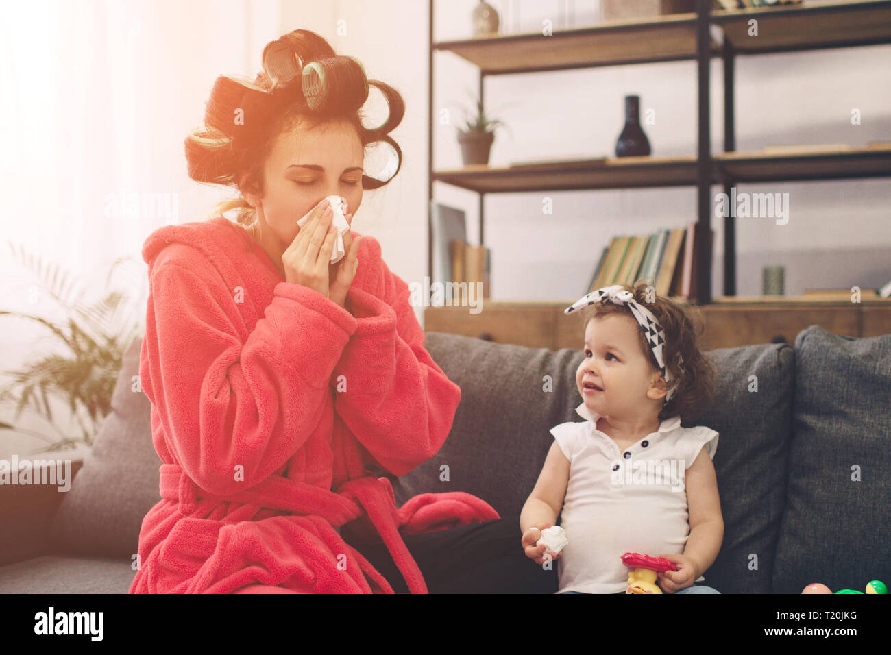 Young mother old is experiencing postnatal depression. Sad and tired woman with PPD. She does not want to play with her daughter. The woman is sick an - Stock Image