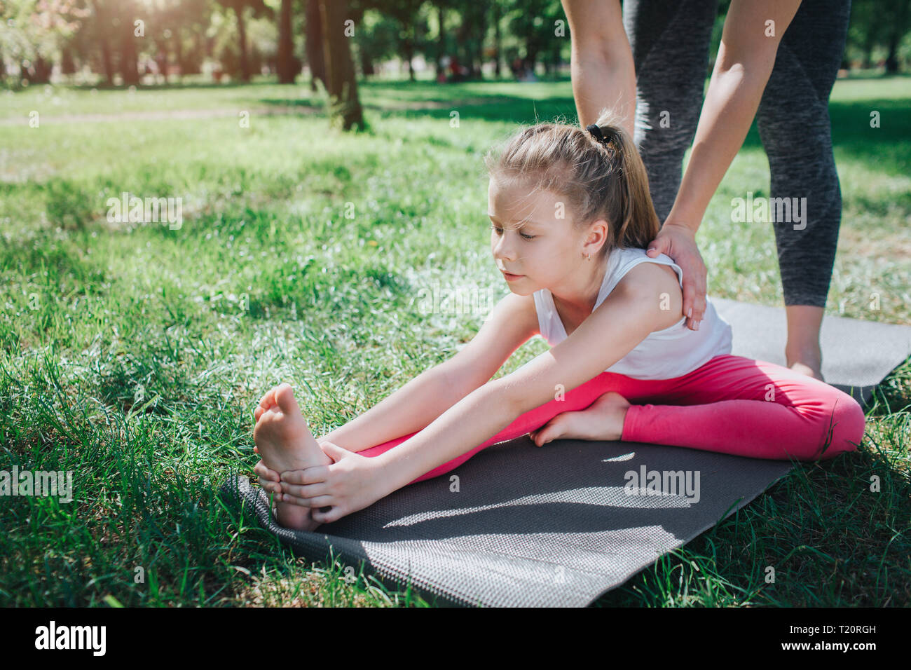 A picture of small girl stratching. Adud woman is helping her to do that right. Girl is keeping her left foot close to right leg. Yoga and Pilates Con - Stock Image