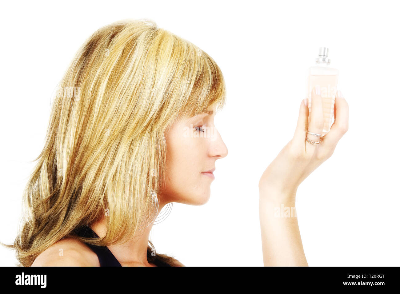 A young woman is enjoying the fragrance of her perfume. Isolated against a white background. - Stock Image