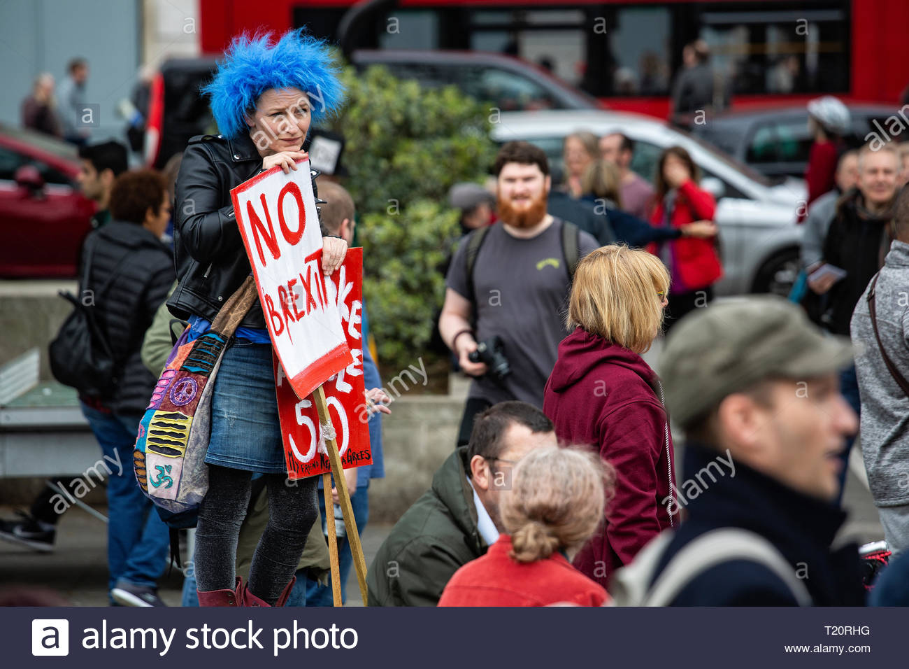 A woman in a blue wig and holding a No Brexit sign looks ruefully at a crown at Marble Arch Stock Photo