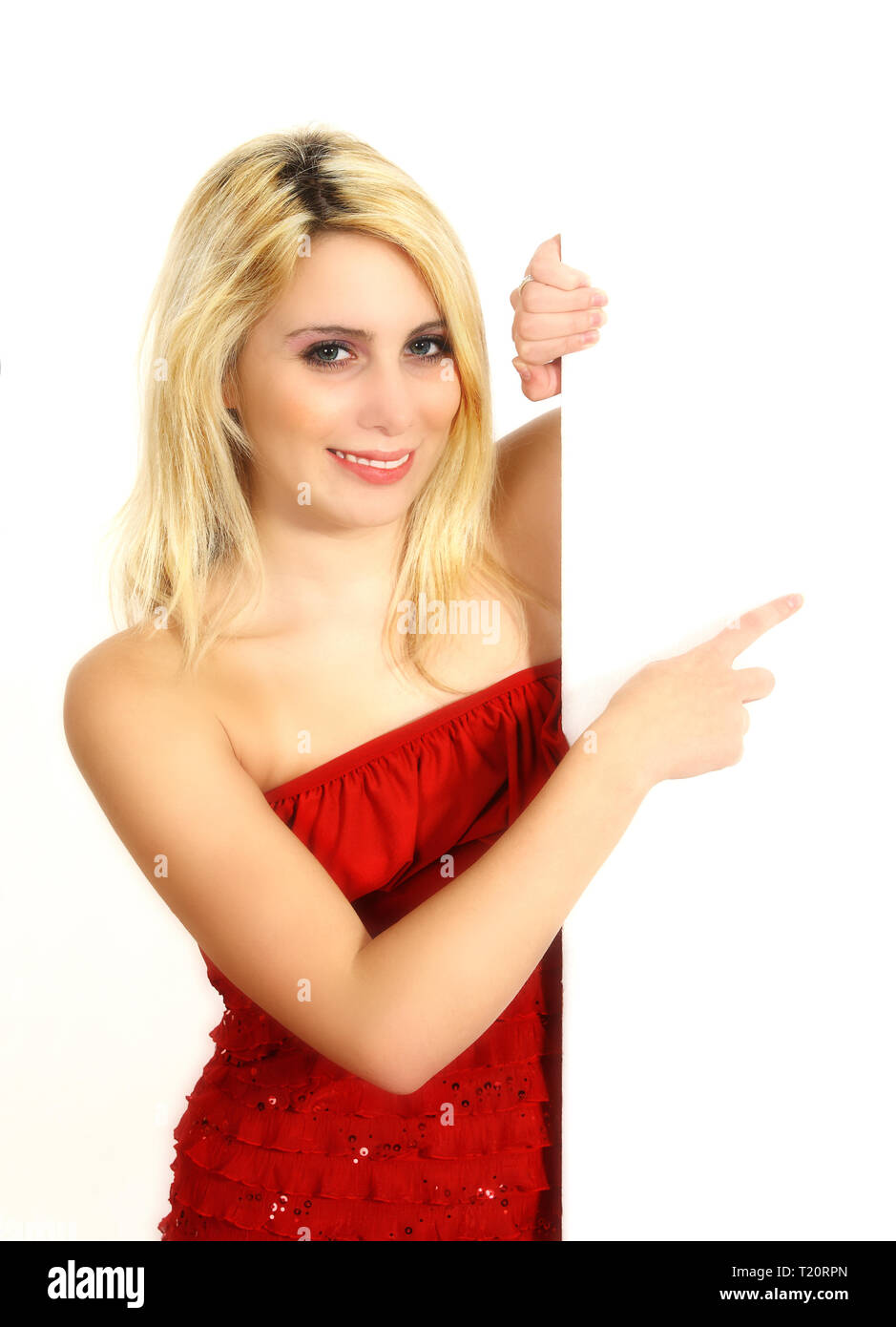 A young woman points her finger at a white free surface. Isolated against a white background. Ideal for presentations. - Stock Image