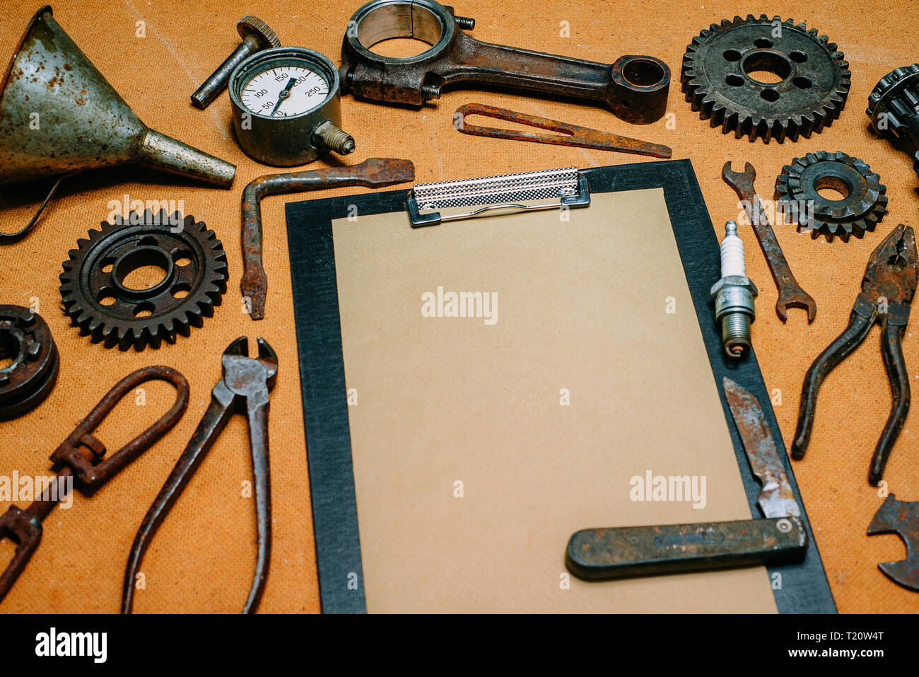 Clipboard with paper for your info in the center of rusty tools, gears on vintage fiberboard background. Motorcycle equipment and repair template. Stock Photo