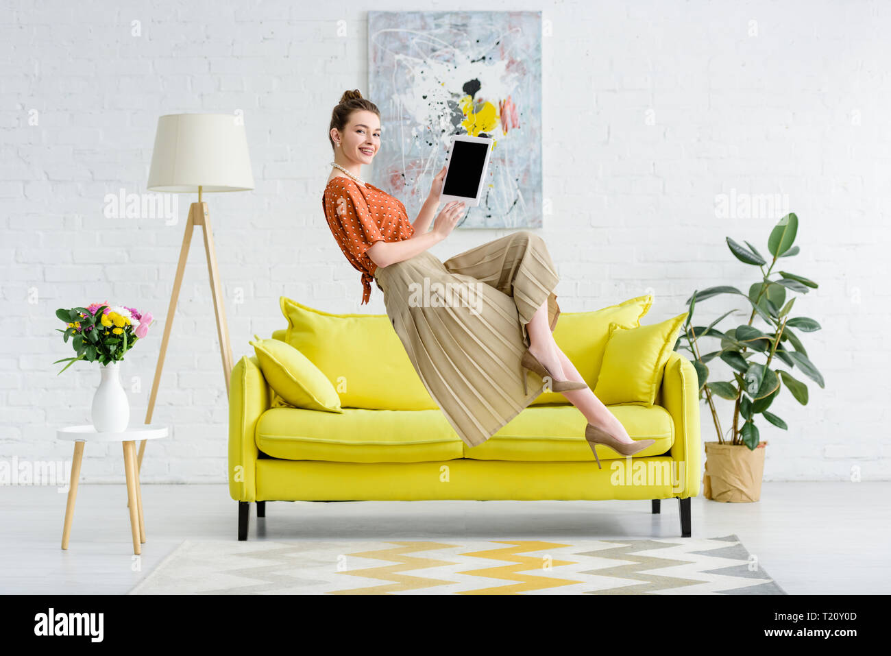 elegant happy young woman levitating in air and showing digital tablet with blank screen in living room - Stock Photo