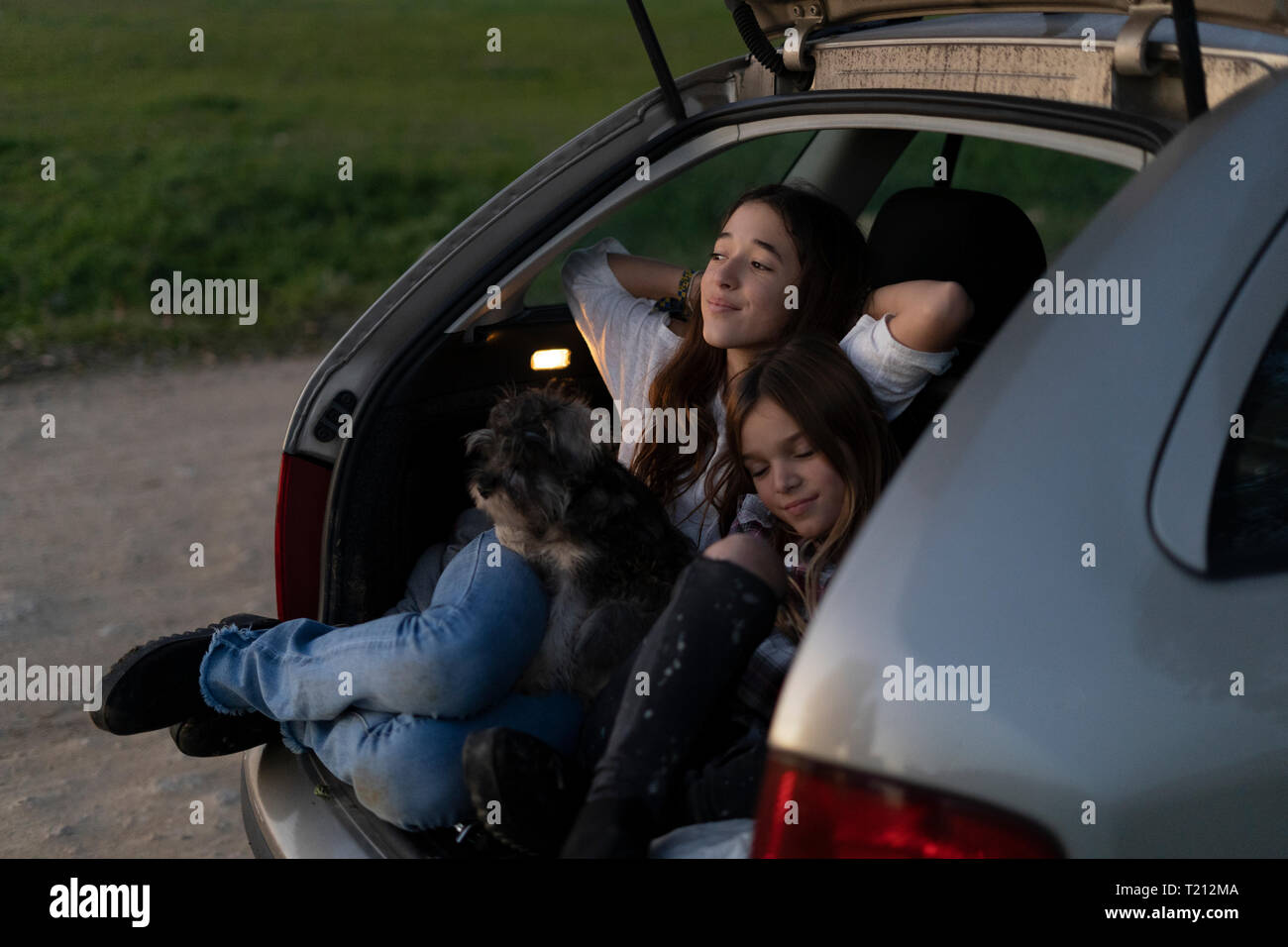 Two sisters in opened boot of parked car watching sunset - Stock Image