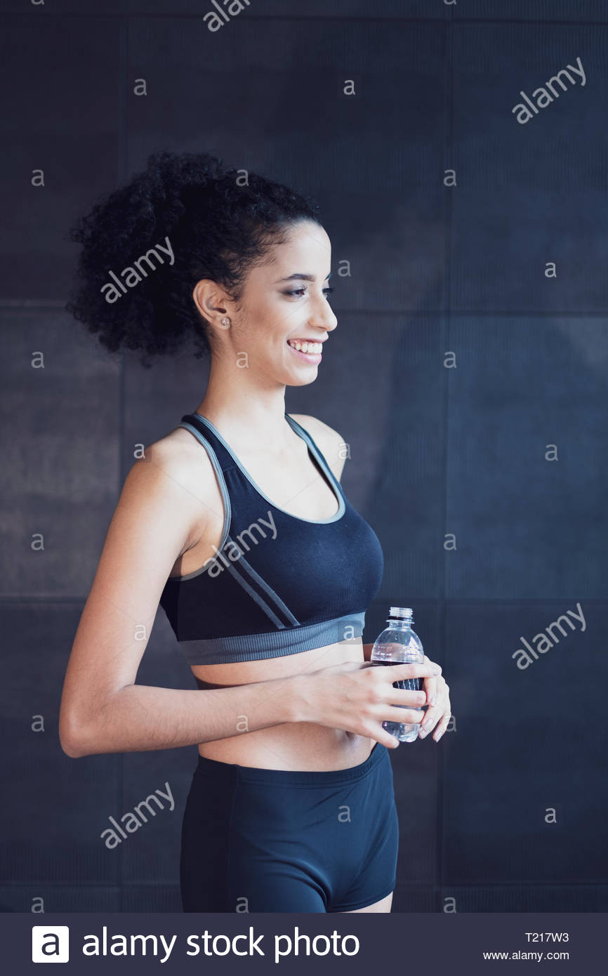 An Afro Latin American woman in sports clothes with a bottle of water indoors - Stock Image