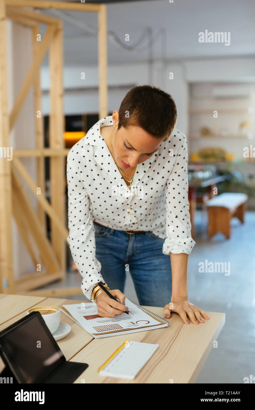 Woman working on draft at desk in office - Stock Image