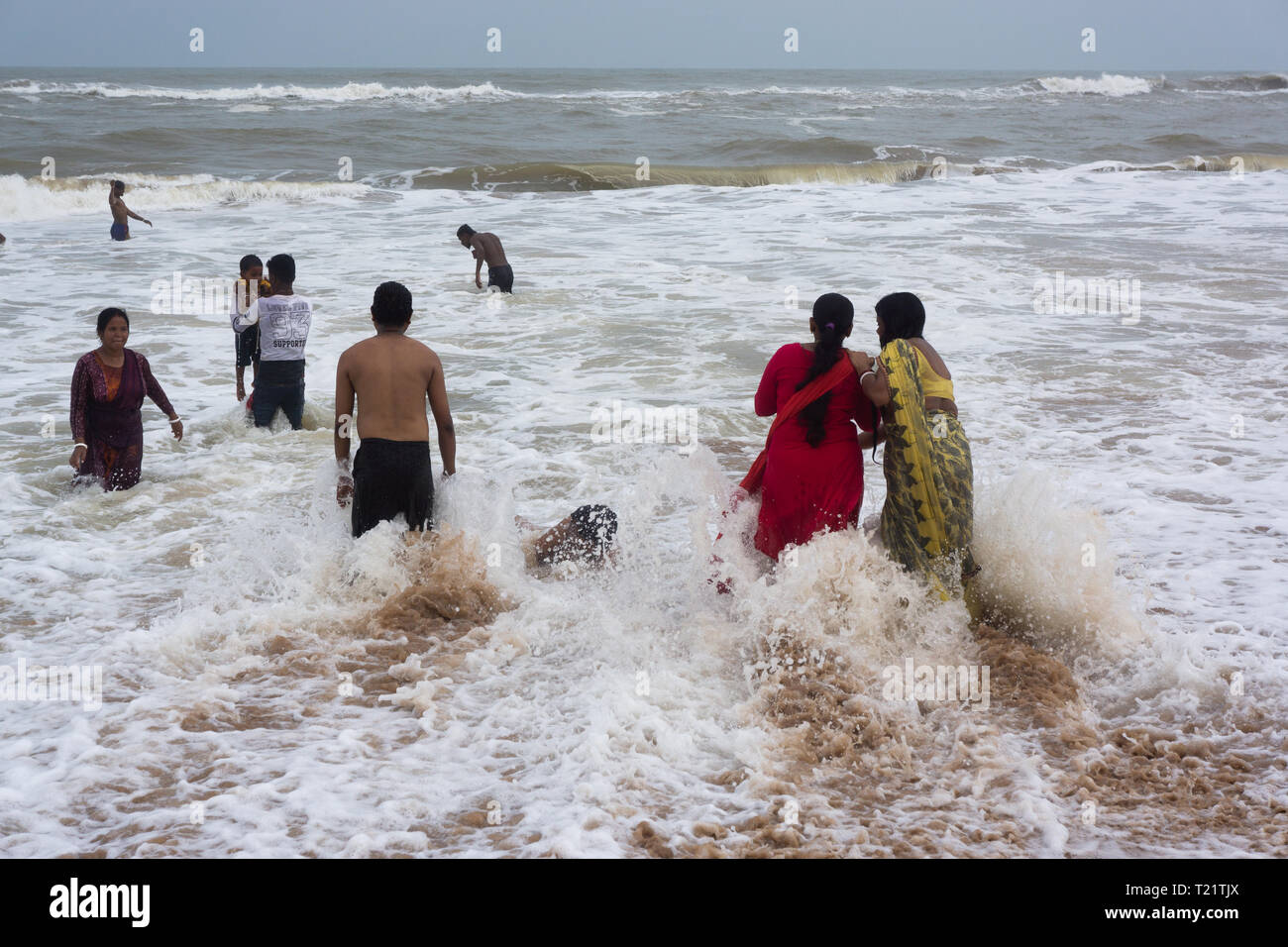 women with Sarees bathing in the sea - Stock Image