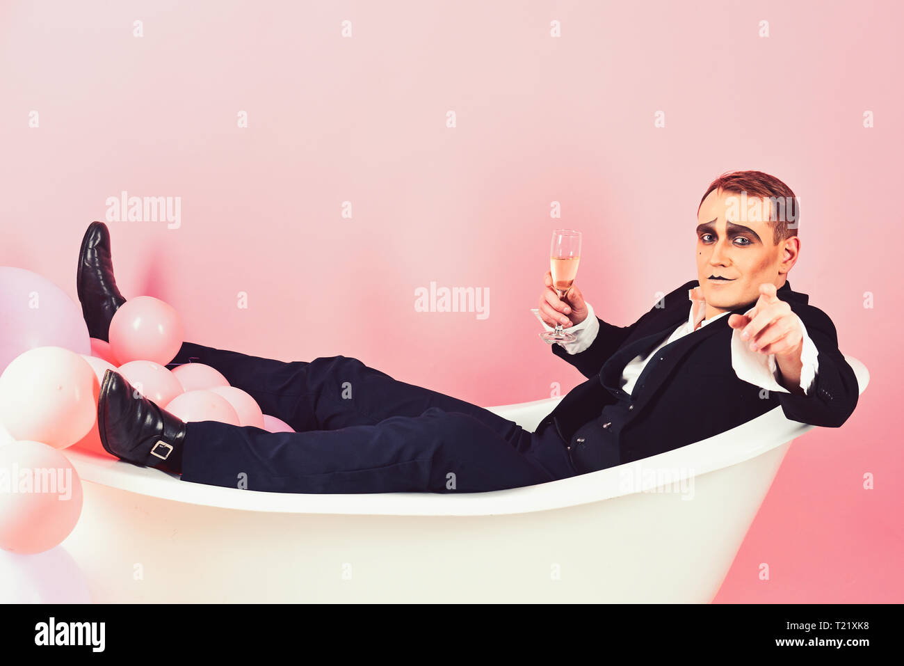 Will you join me. Mime actor enjoy bathing in bath tub. Bathing and relaxing. Mime man has celebration party with champagne. Comedian actor celebrate - Stock Image