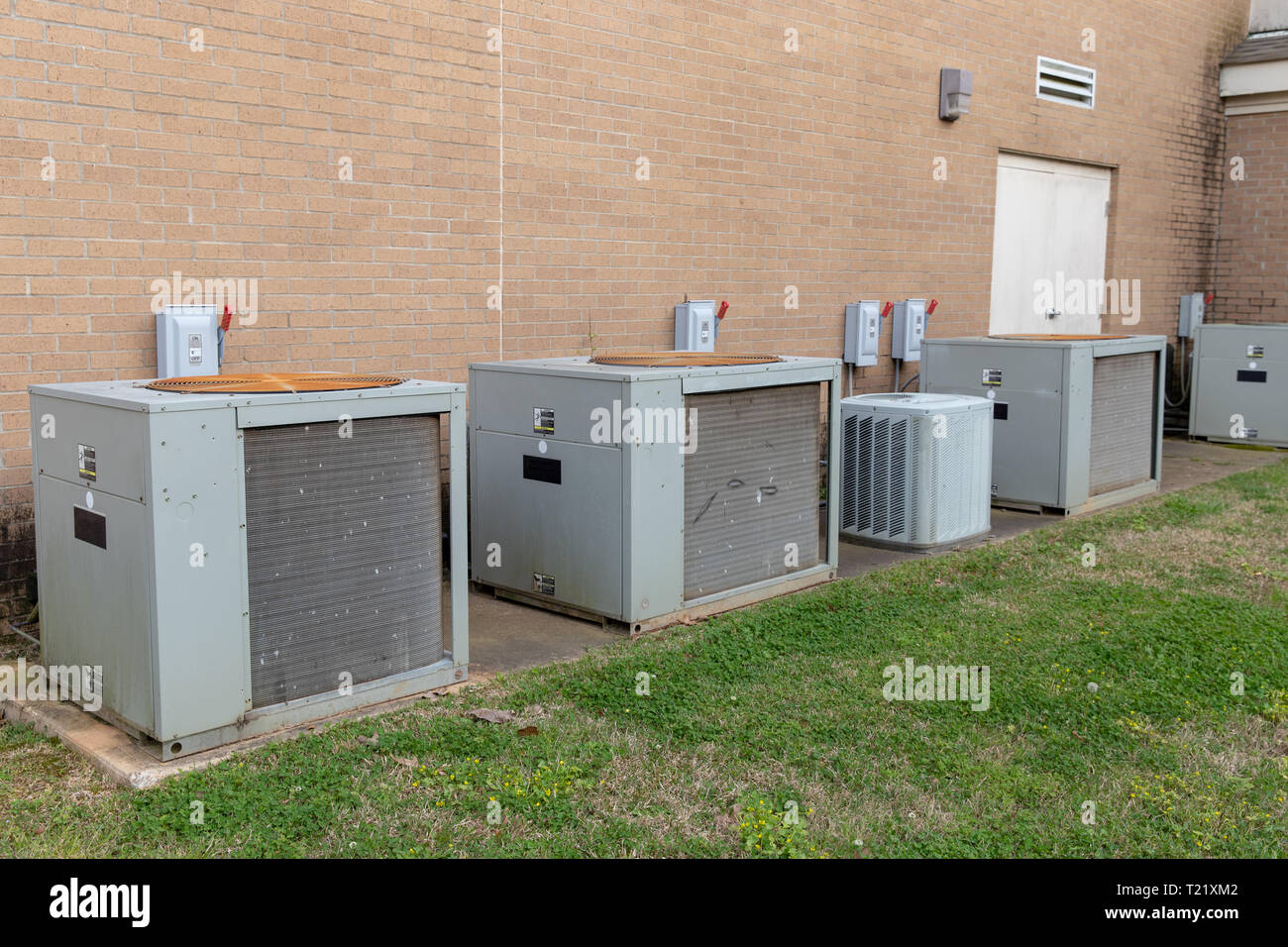 Commercial Air Conditioner compressors outside of brick building Stock Photo