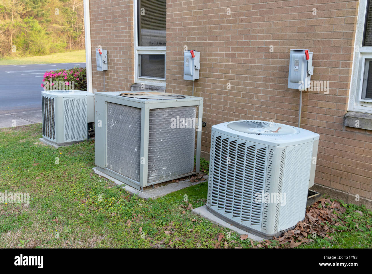 3 Air Conditioner Compressors outside commercial building with cutoff switches. Stock Photo
