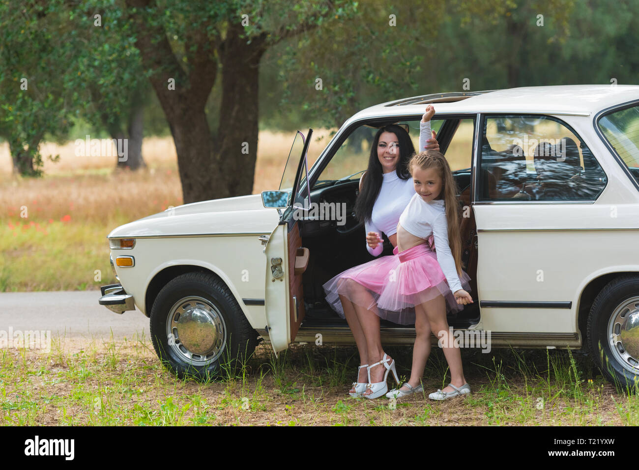 Happy family on a road trip in their car. Mom and daughter are traveling by car. Summer ride by automobile - Stock Image