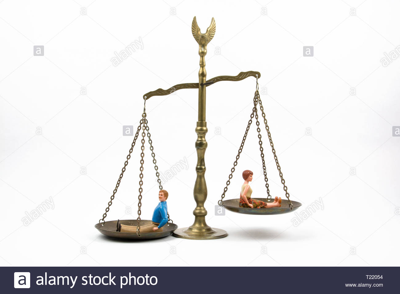 An image of the scales of justice with a man and a woman sitting on the scales. The man carries more weight than the woman, a symbol of inequality. - Stock Image
