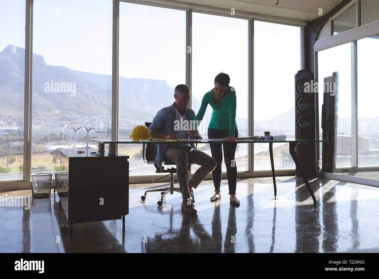 Architectures discussing over blue print at desk in office - Stock Image