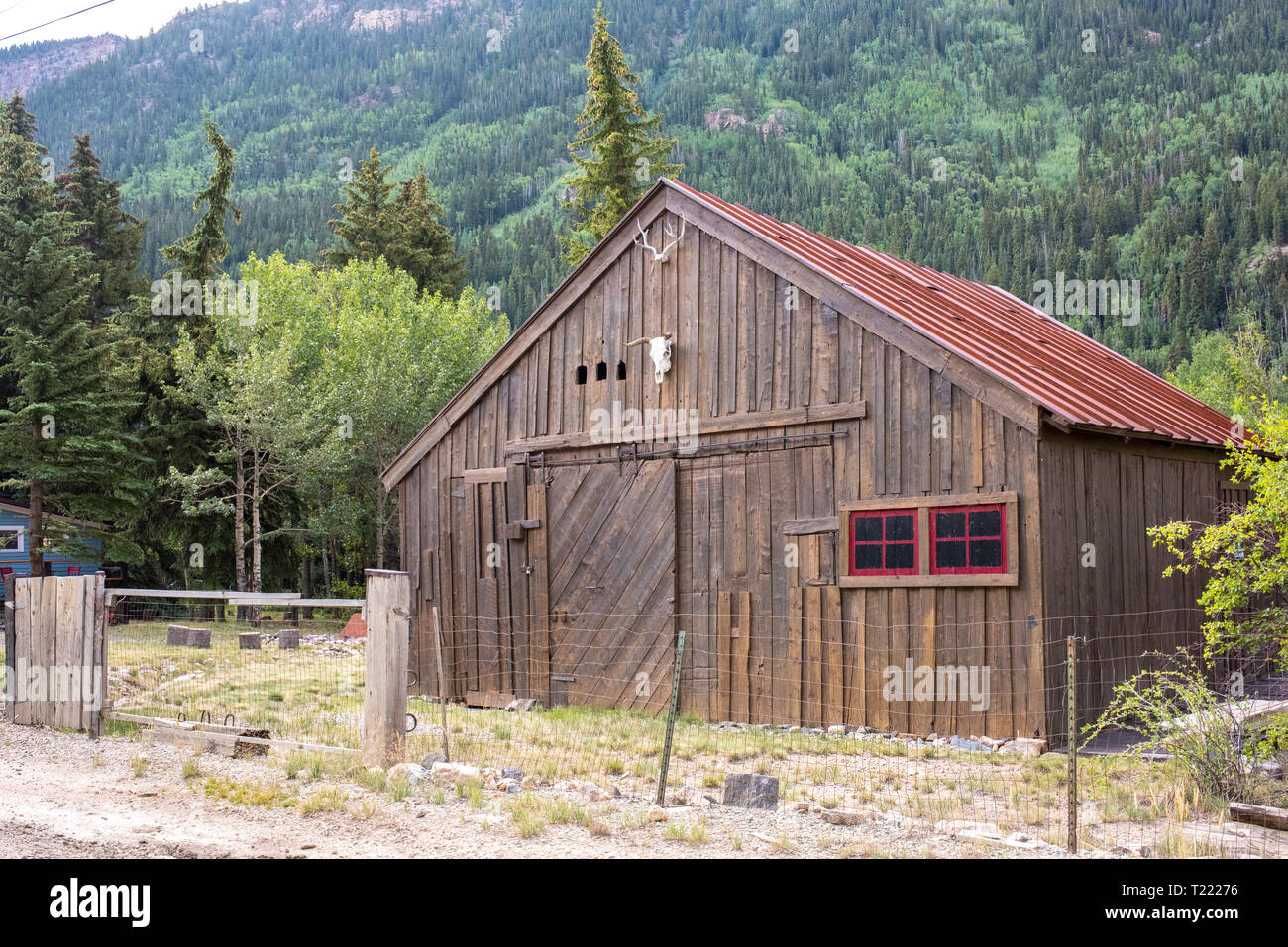 A rustic bar with red trim sits beside a large hill in Silver Plume, Colorado. Stock Photo