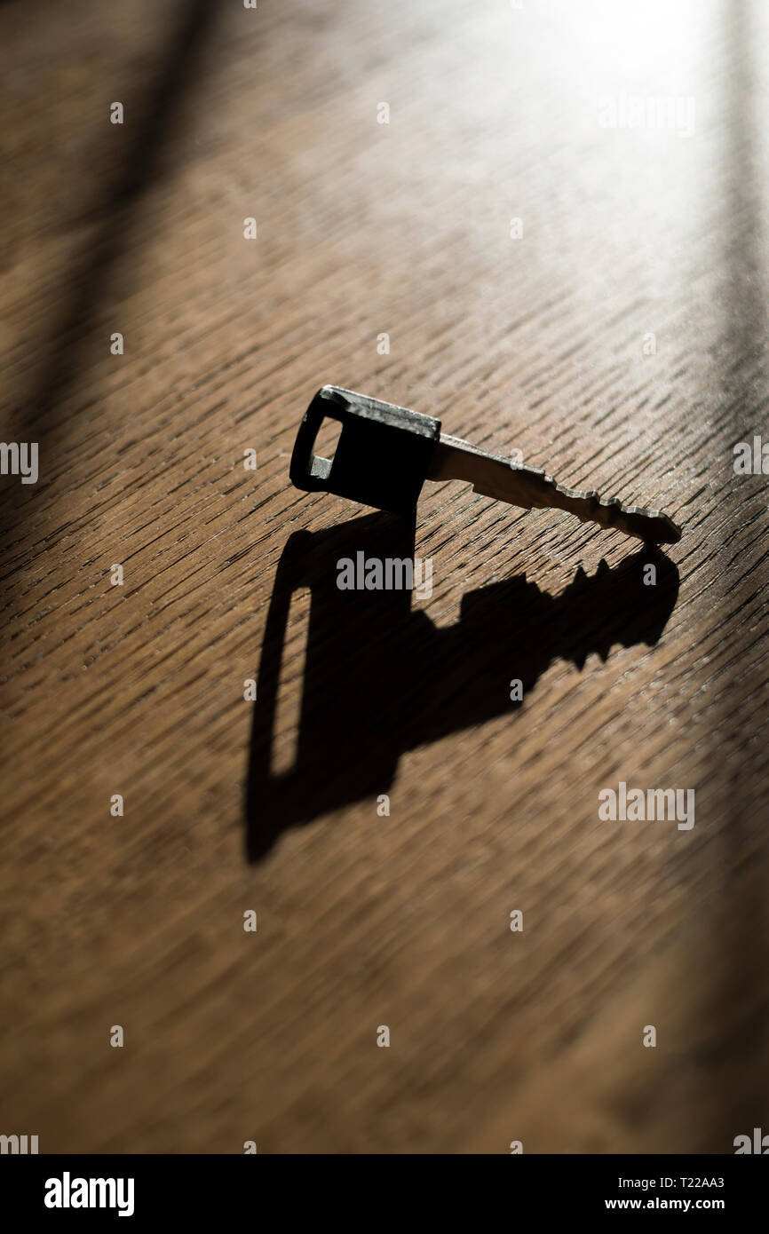 Car key casting a shadow on a wooden table Stock Photo
