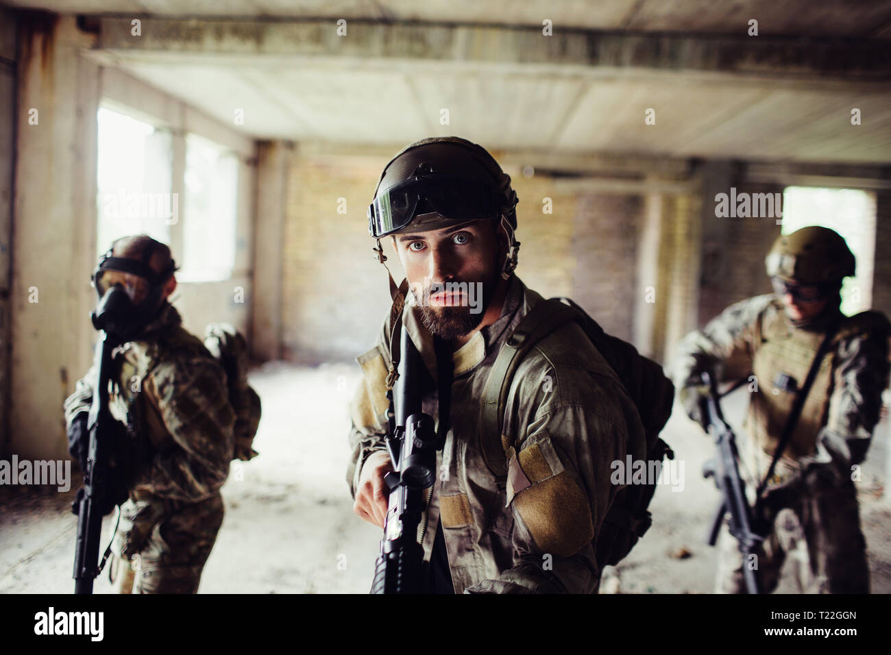 Warriors are standing in empty room. They are going forward very careful. Guys on the back wear special face masks. They are protect themselves with s - Stock Image