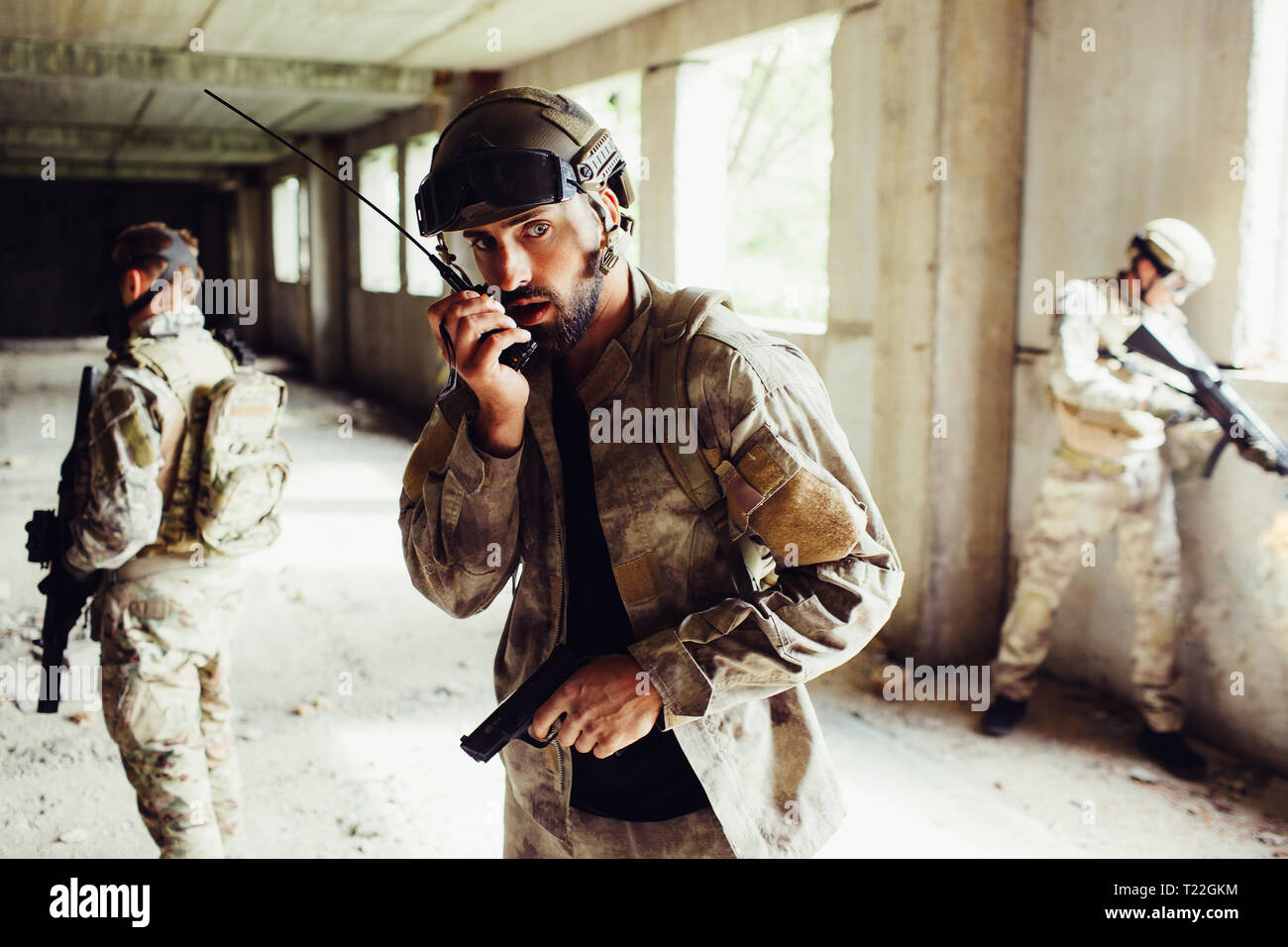 A pictur of guy standing in empty room with other warriors. He is holding gun and talking to portable radio. He is looking straight. Other guys are gu - Stock Image