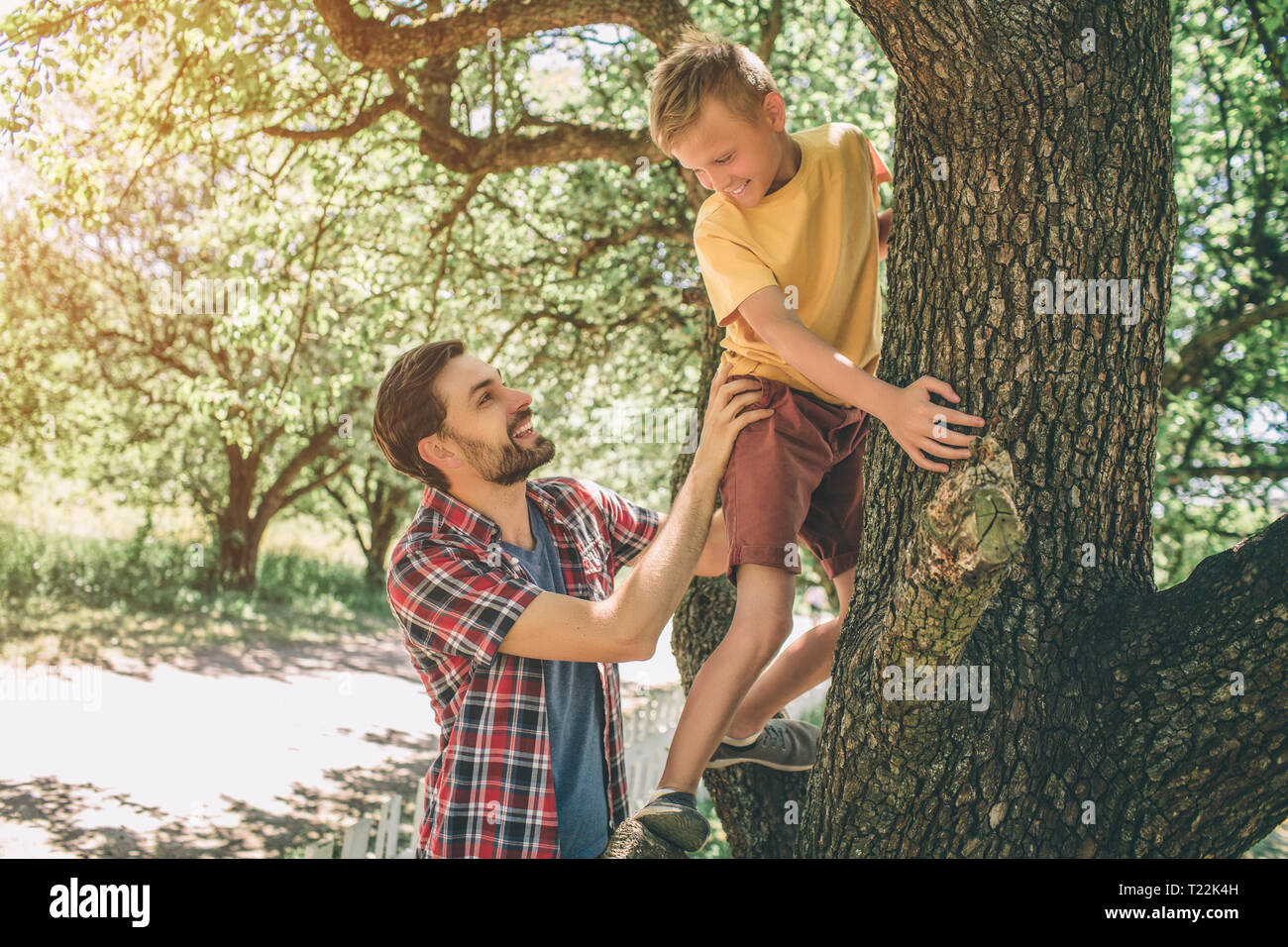 Father and son are playing with each other. Guy is supporting his child. Boy is looking down at father. They are smiling. Both of them are happy Stock Photo