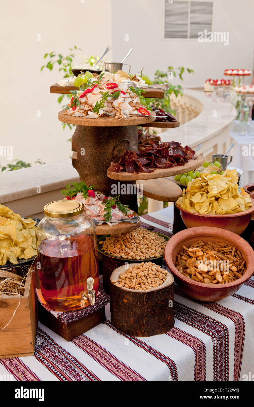 Delicious wedding reception table with snacks, peanuts, crackers, chips, basturma, fat and moonshine on the Cossack table - Stock Image