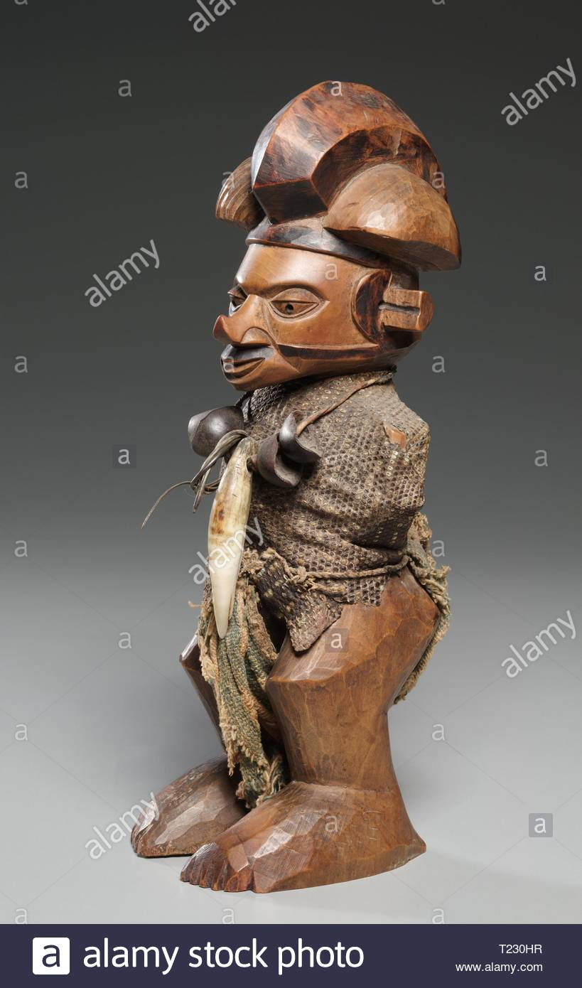 Figure, late 1800s-mid 1900s. Central Africa, Democratic Repulic of the Congo, late 19th-mid 20th Century. Wood, lizard skin, leopard tooth, seed pods, cloth; overall: 23 cm (9 1/16 in.). - Stock Image