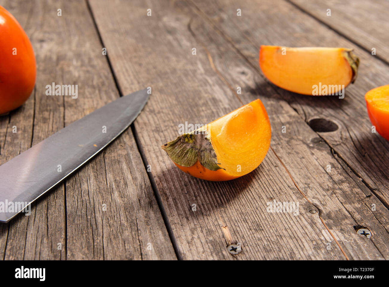 Particle of persimmon with knife on retro wooden table, vitamins - Stock Image