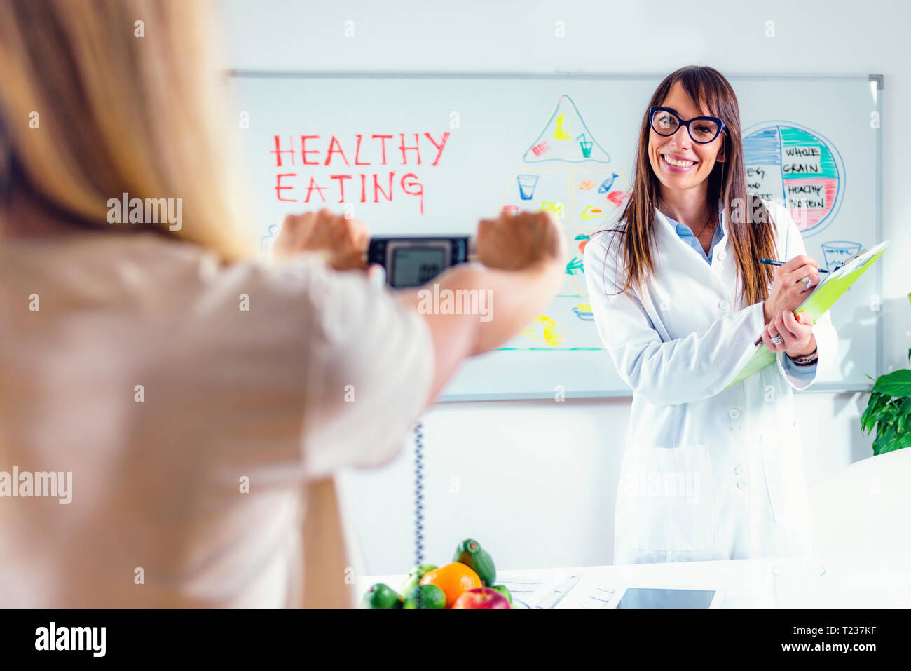 Measuring body fat with electronic scales. - Stock Image