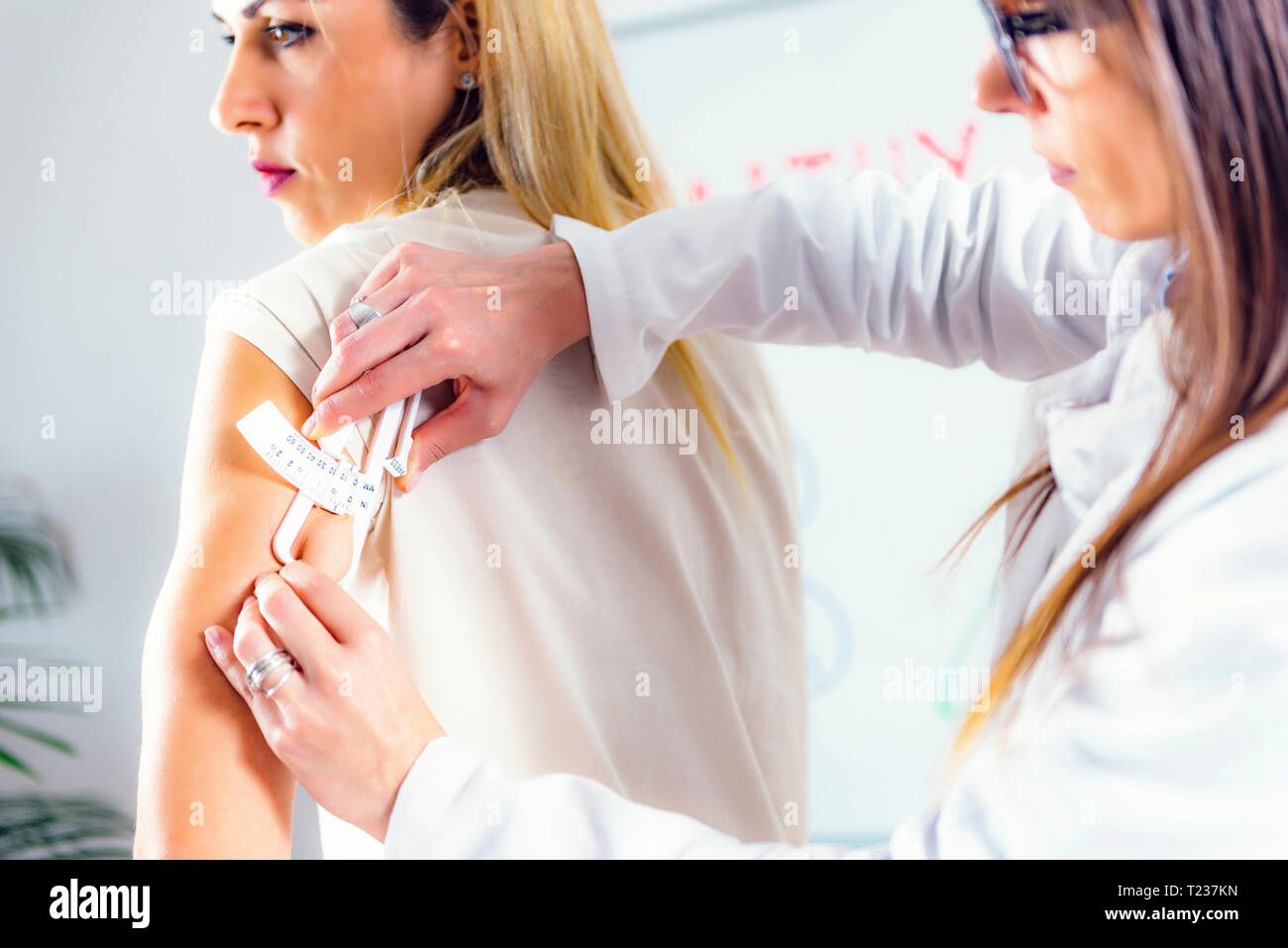 Nutritionist measuring female patient's body fat with callipers. - Stock Image