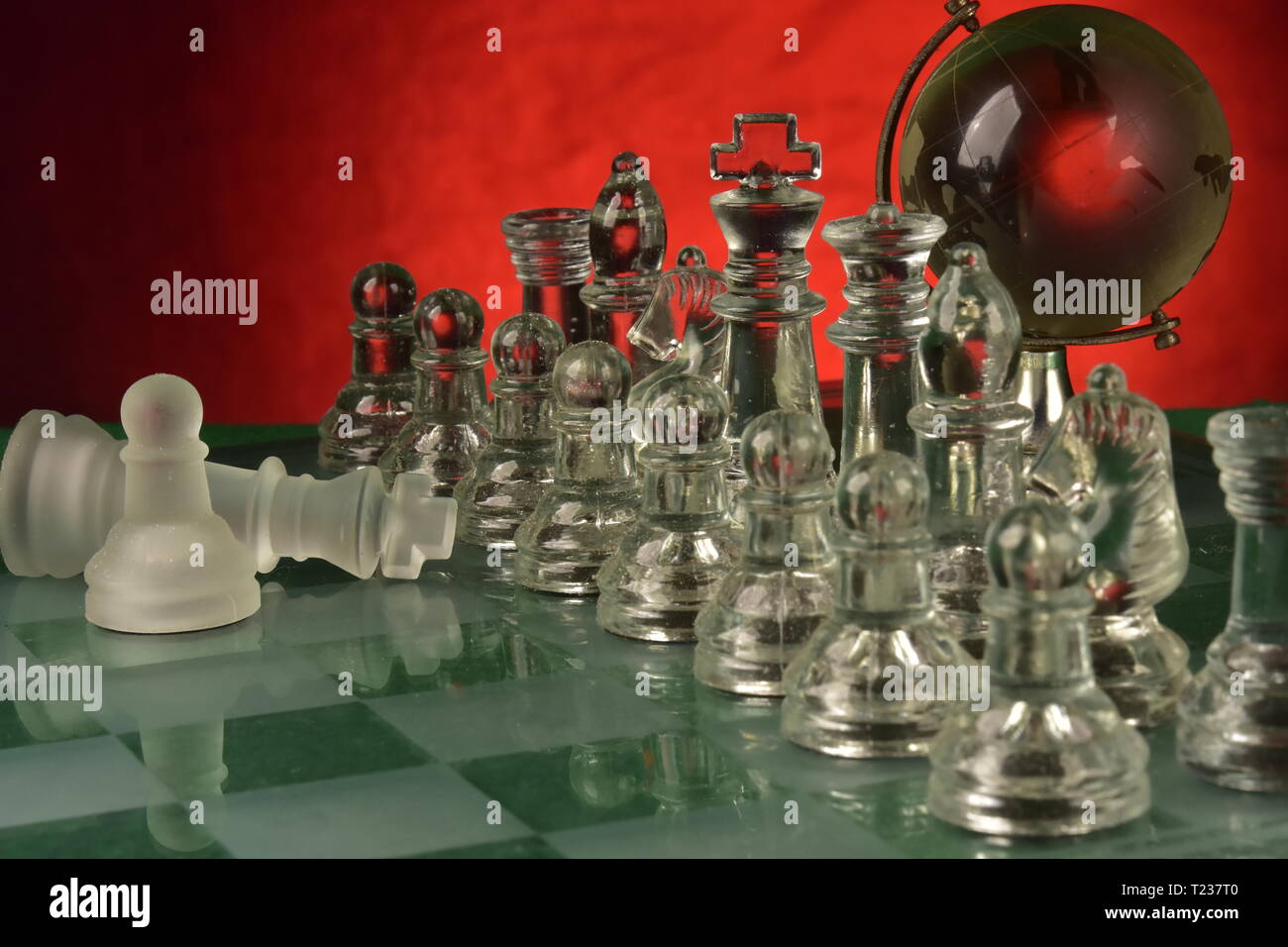 Chessboard table with glass pieces and red background - Stock Image
