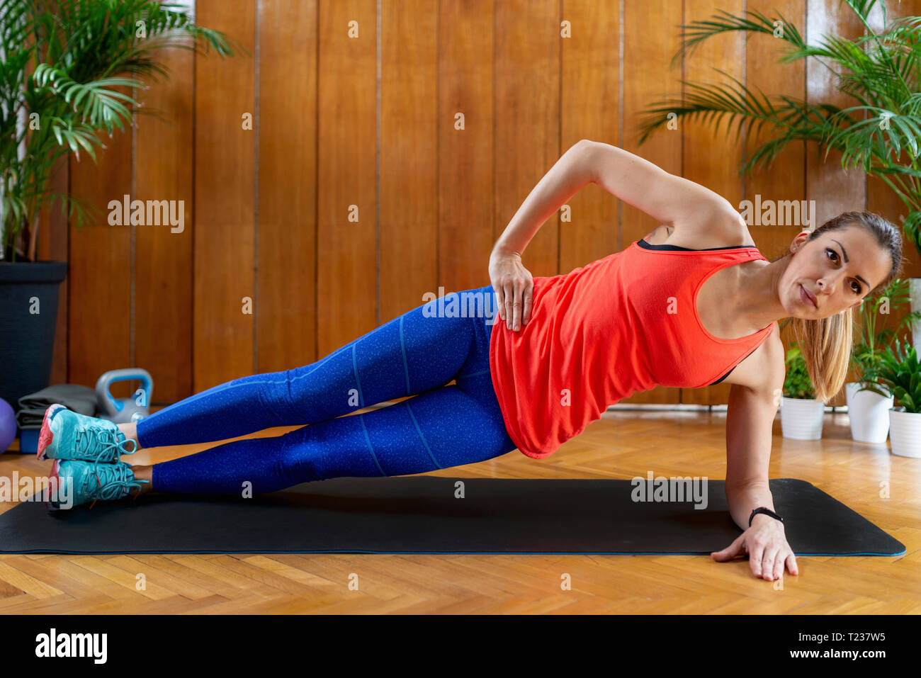 Woman doing High-intensity interval training at home. Woman Doing Side Plank Exercise. - Stock Image