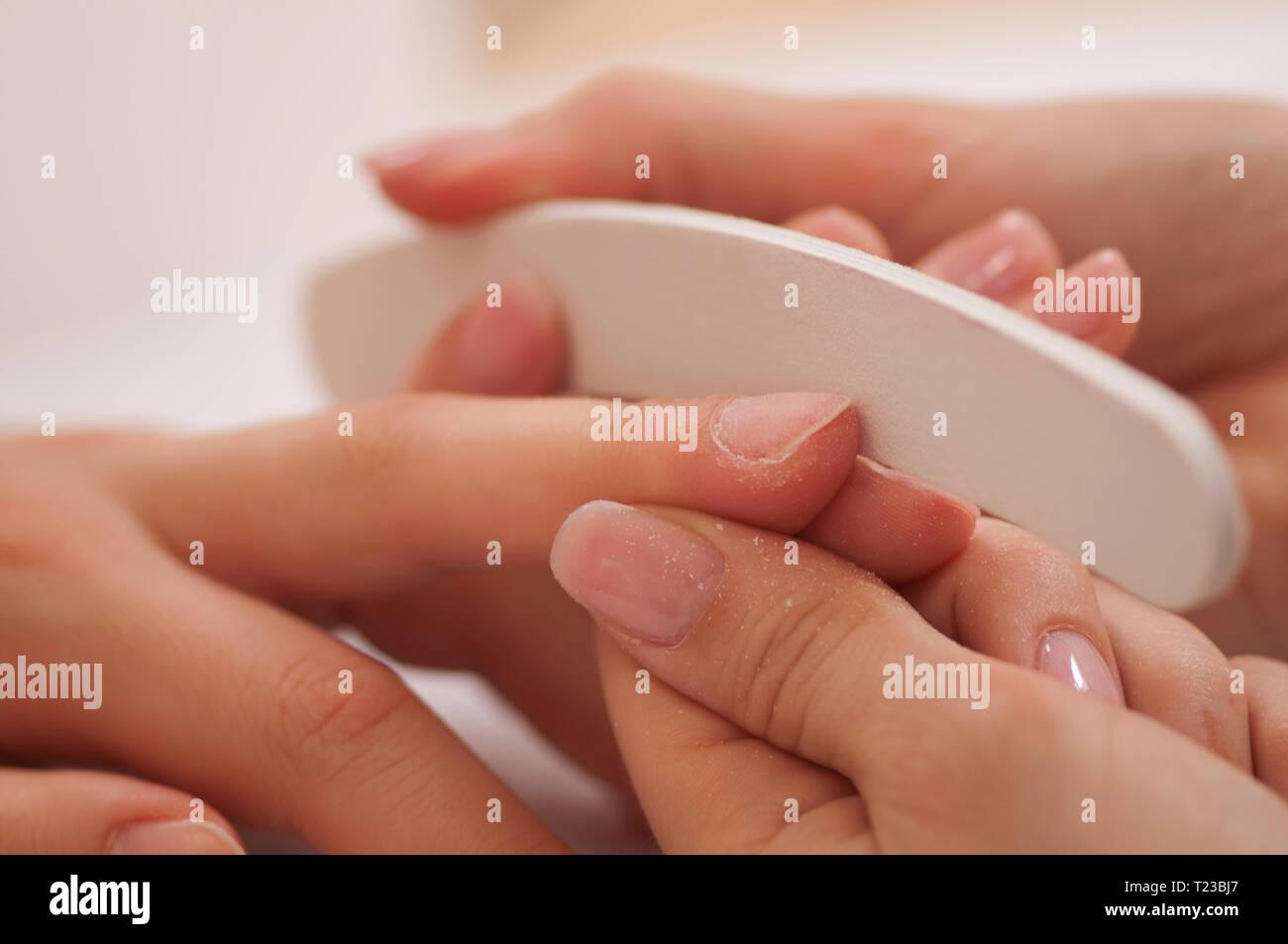 Using nail buffer at nail salon. - Stock Image