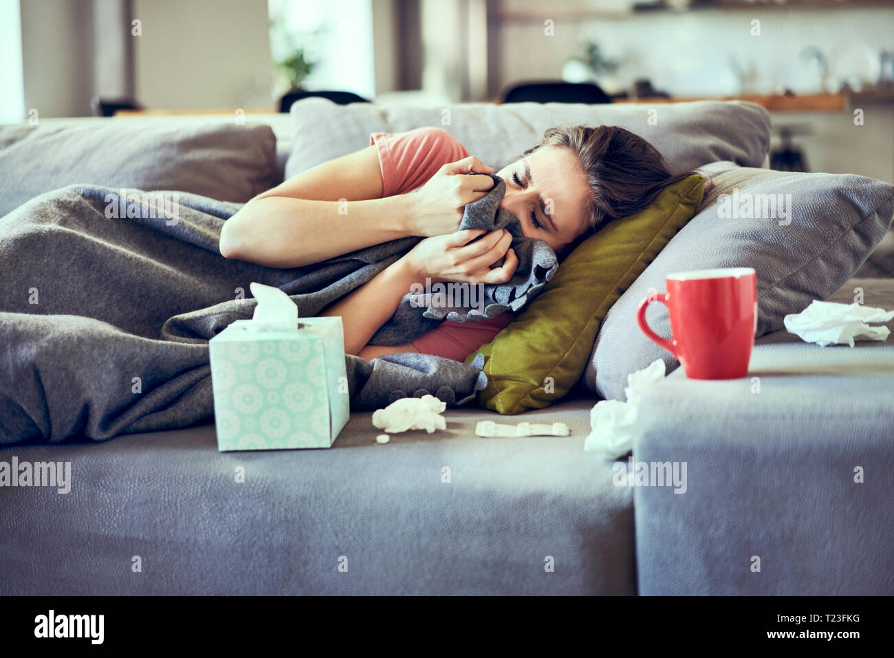 Sick woman trying to take a nap while lying on couch covered in blanket - Stock Image